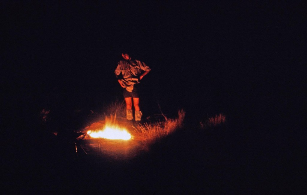 QM photographer Jeff Wright looks after the campfire in dry creek bed.